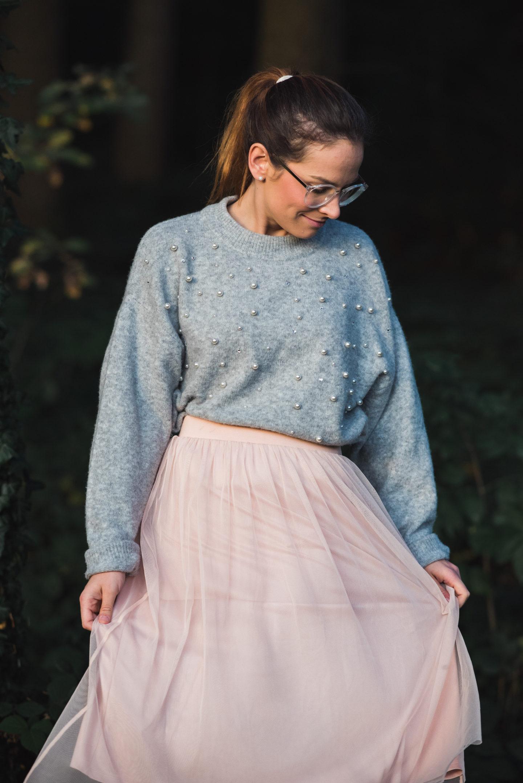 Frau mit rosa Jupe und grauem Perlenpulli