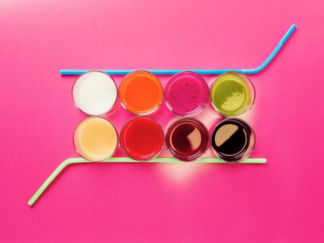Verschiedenfarbige Getränke und Strohhalme