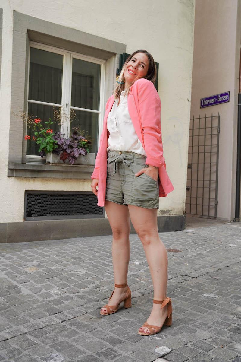 Frau mit kurzen Hosen und rosa Blazer